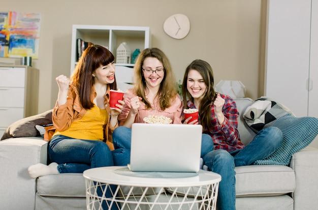Gelukkige jonge meisjes of voetbalfans die popcorn eten terwijl ze voetbal kijken op laptop en de overwinning vieren. vriendschap, sport en entertainment concept.