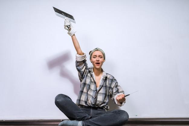 Gelukkige jonge meisjesbouwer zit op de vloer, houdt een spatel vast, maakt reparaties in het appartement
