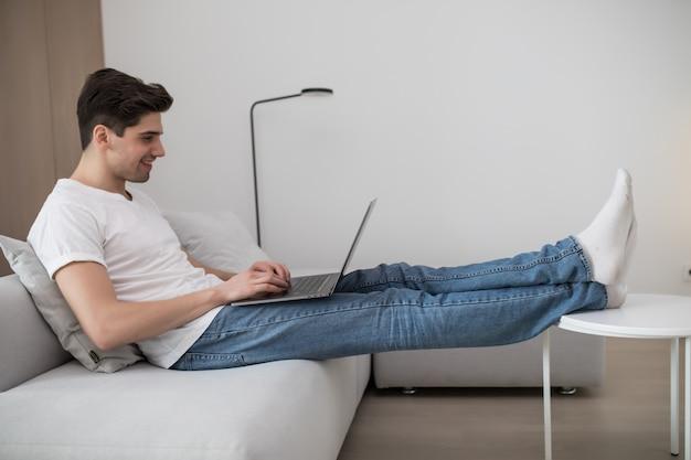 Gelukkige jonge mens die aan zijn laptop op de bank thuis werkt