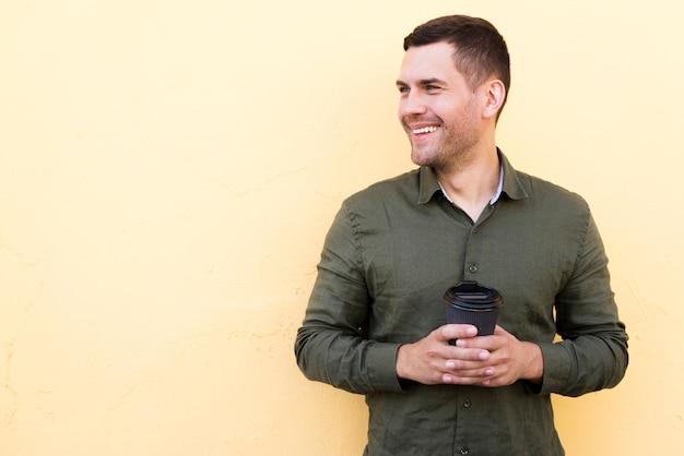 Gelukkige jonge mens die beschikbare koffiekop houden die weg over beige achtergrond kijken