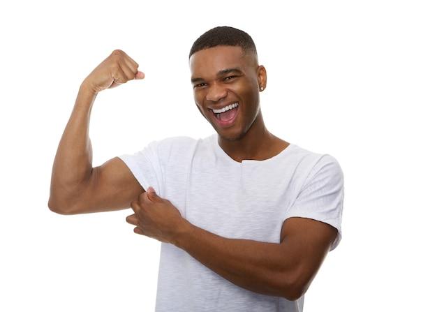 Gelukkige jonge mens die bicep spier buigt