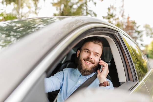 Gelukkige jonge mens die door auto reist die mobiele telefoon met behulp van