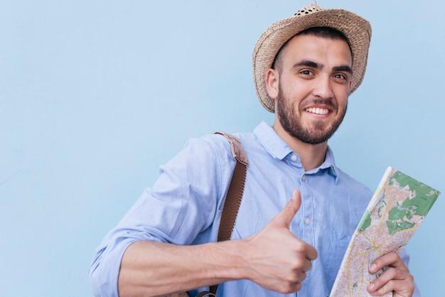 Gelukkige jonge mens die duim op gebaar tonen en kaart houden tegen blauwe achtergrond