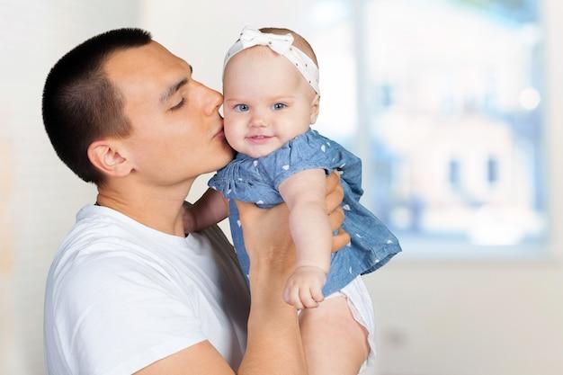Gelukkige jonge mens die een baby houdt