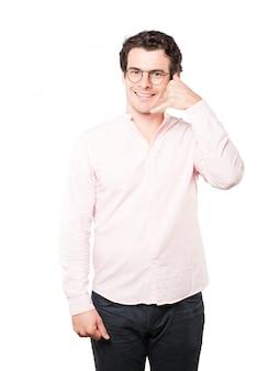 Gelukkige jonge mens die een gebaar van het roepen met de hand maakt