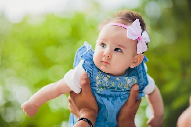 Gelukkige jonge mens die een glimlachende 2-4 maanden oudbaby op een achtergrond van bladeren houdt niet in nadruk
