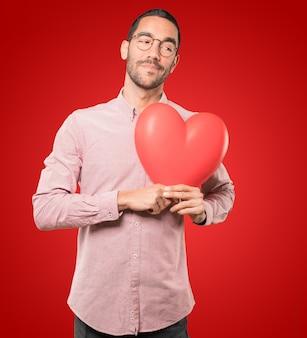 Gelukkige jonge mens die een groot stuk speelgoed hart houdt en gebaren doet over de dag van valentine