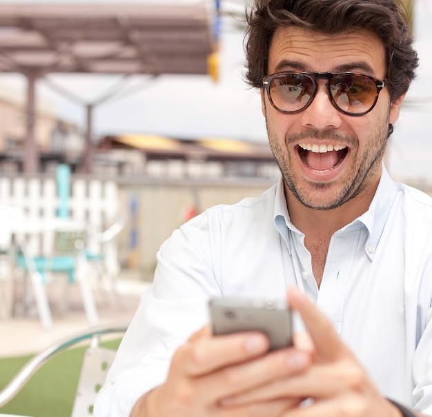 Gelukkige jonge mens die een mobiele telefoon met behulp van