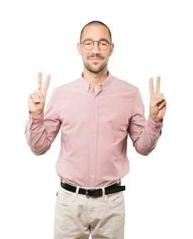 Gelukkige jonge mens die een overwinningsgebaar met zijn vingers maakt