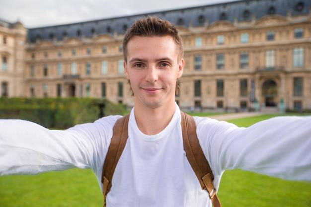 Gelukkige jonge mens die een selfiefoto in parijs, frankrijk nemen