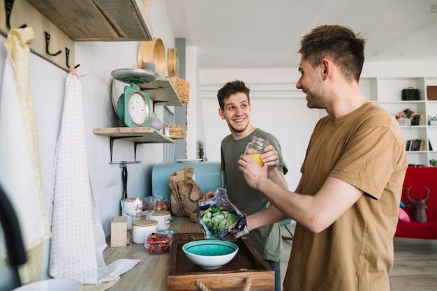 Gelukkige jonge mens die elkaar voor thuis het voorbereiden van ontbijt helpen