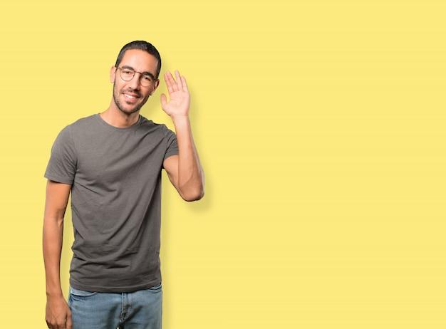 Gelukkige jonge mens die en een gebaar glimlachen van het proberen om iets te horen