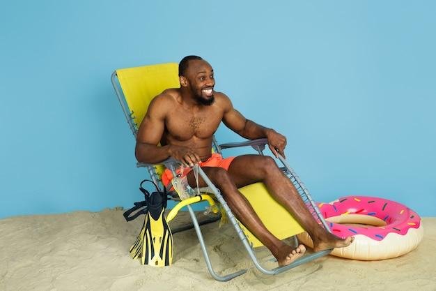 Gelukkige jonge mens die en met strandring als doughnut op blauwe studioachtergrond rusten lacht. concept van menselijke emoties, gezichtsuitdrukking, zomervakantie of weekend. chill, zomer, zee, oceaan.