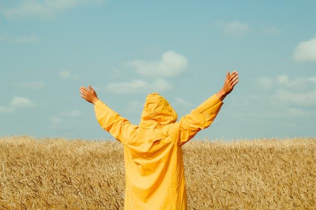 Gelukkige jonge mens die gele regenjas draagt die zich op een tarwegebied bevindt