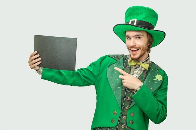 Gelukkige jonge mens die in groen kostuum zwart stuk van document houdt. hij draagt het pak van sint patrick. geïsoleerd op grijs.