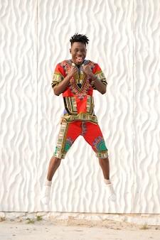 Gelukkige jonge mens die in nigeriaanse nationale kleren op een witte muur springt