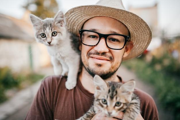 Gelukkige jonge mens die in strohoed aanbiddelijk katje twee houdt