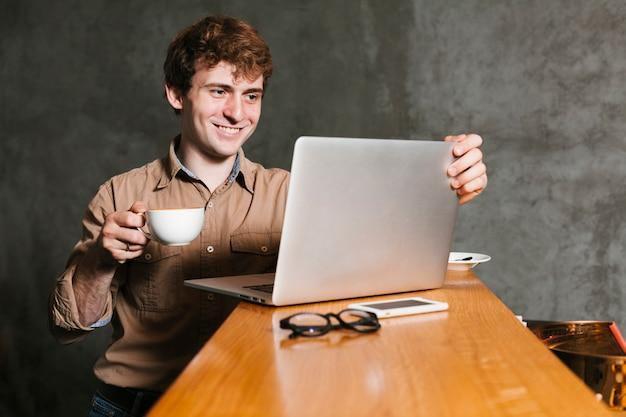 Gelukkige jonge mens die laptop bekijkt
