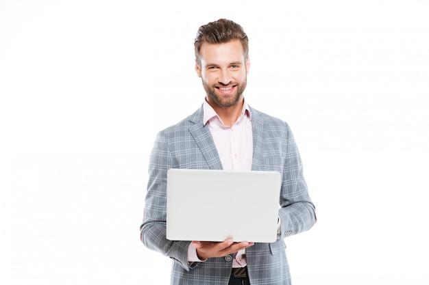 Gelukkige jonge mens die laptop computer met behulp van
