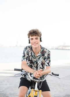 Gelukkige jonge mens die met fiets aan muziek op hoofdtelefoon luistert