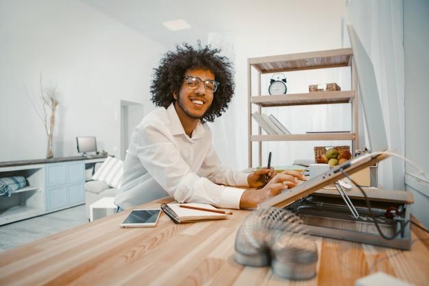Gelukkige jonge mens die met laptop thuis werkplaats werkt
