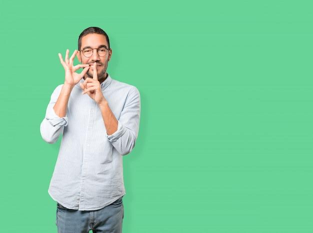 Gelukkige jonge mens die om stilte vragen die met zijn vinger gesturing