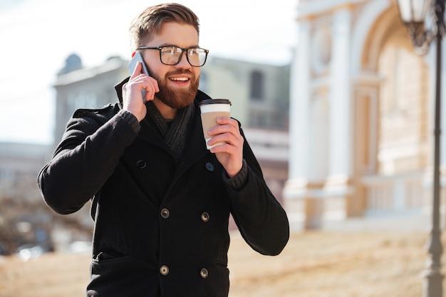 Gelukkige jonge mens die op celtelefoon spreekt en koffie drinkt