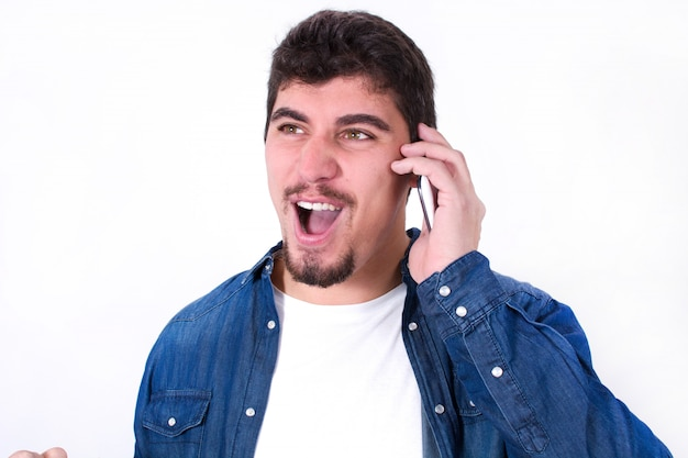 Gelukkige jonge mens die op mobiele geïsoleerde telefoon spreekt