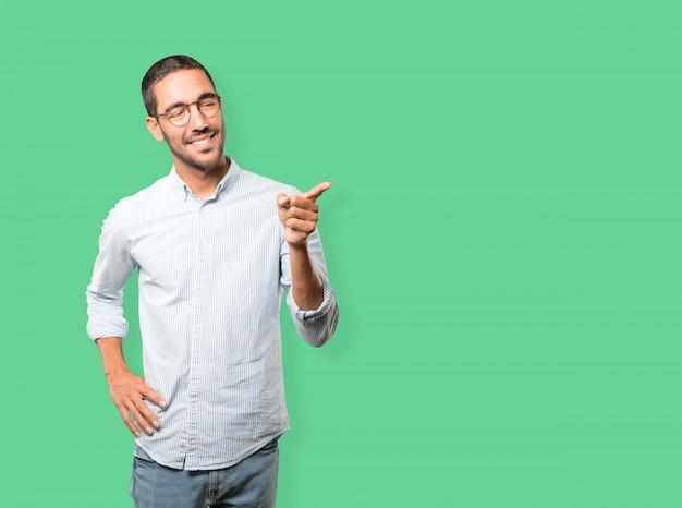 Gelukkige jonge mens die op u met zijn vinger richt