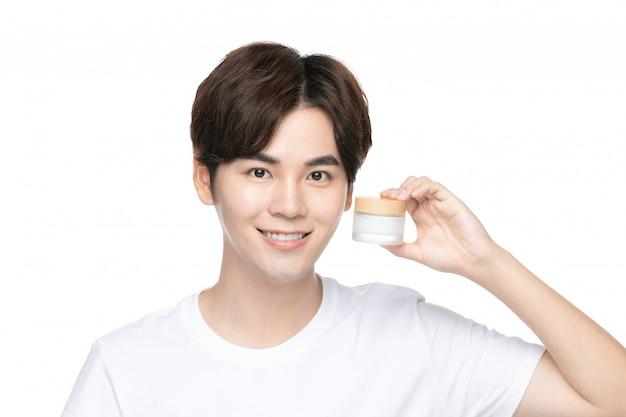 Gelukkige jonge mens die room op zijn gezicht gebruikt tegen witte muur