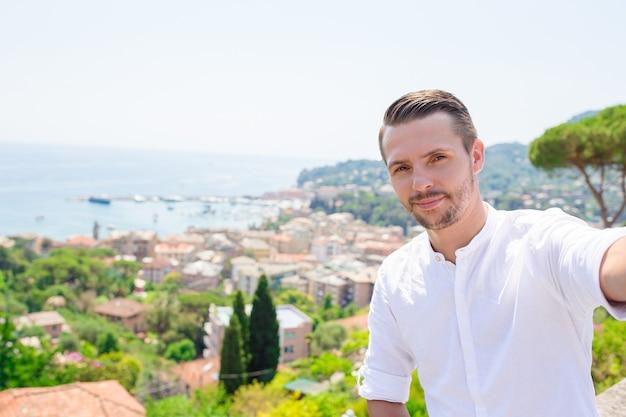 Gelukkige jonge mens die selfie op de oude kuststad rapallo in ligurië nemen