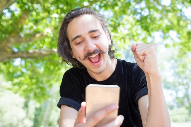 Gelukkige jonge mens die smartphone in park bekijken.