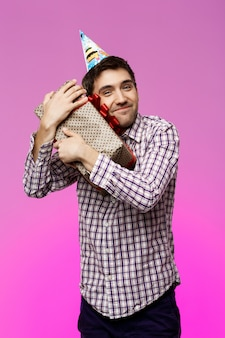 Gelukkige jonge mens die verjaardagsgift in doos over purpere muur omhelst.