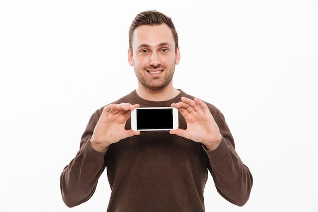 Gelukkige jonge mens die vertoning van mobiele telefoon toont