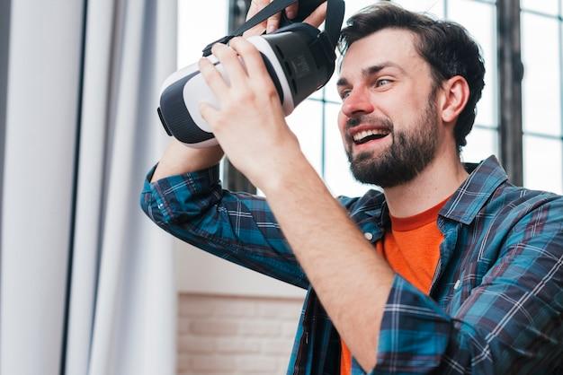 Gelukkige jonge mens die virtuele werkelijkheidsbeschermende brillen draagt