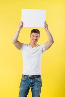 Gelukkige jonge mens die zijn wapens opheft die wit aanplakbiljet tonen tegen gele achtergrond