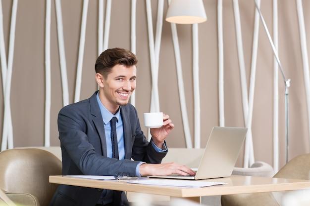Gelukkige jonge mens het drinken koffie en werken in cafe