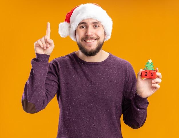 Gelukkige jonge mens in purpere sweater en santahoed die stuk speelgoed kubussen met nummer vijfentwintig toont die vrolijk toont wijsvinger die zich over oranje muur bevindt
