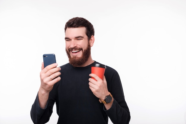 Gelukkige jonge mens in toevallige status over witte achtergrond en gebruikend smartphone en houdend kop van koffie om te gaan