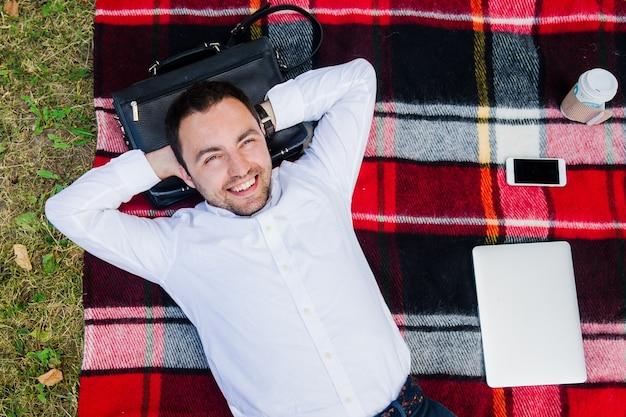 Gelukkige jonge mens met laptop het ontspannen op het gras, mening vanaf de bovenkant