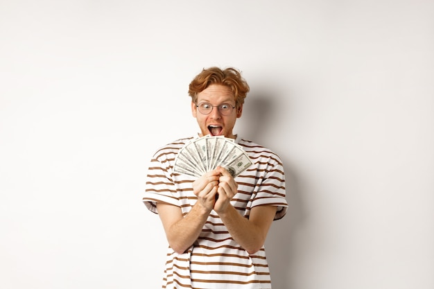 Gelukkige jonge mens met rood haar die dollars tonen, geld winnen en van geluk schreeuwen, prijzengeld houden, die zich over witte achtergrond bevinden.