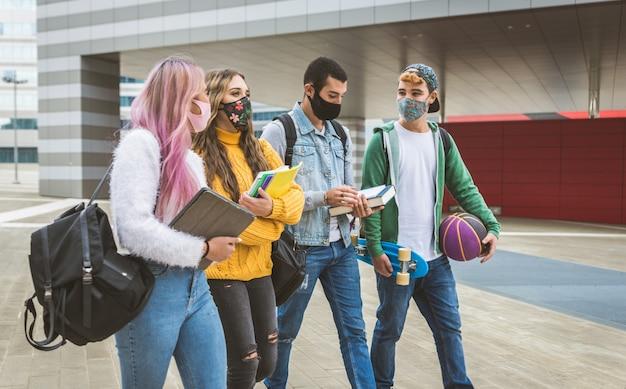 Gelukkige jonge mensen die buiten samenkomen en gezichtsmaskers dragen tijdens covid-19 pandemie