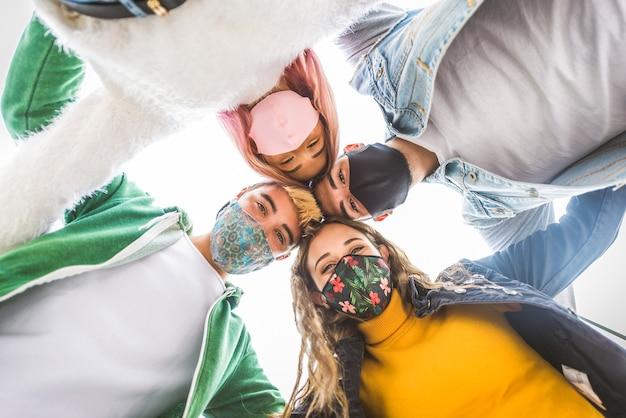 Gelukkige jonge mensen die buiten samenkomen en gezichtsmaskers dragen tijdens covid19 pandemie Premium Foto