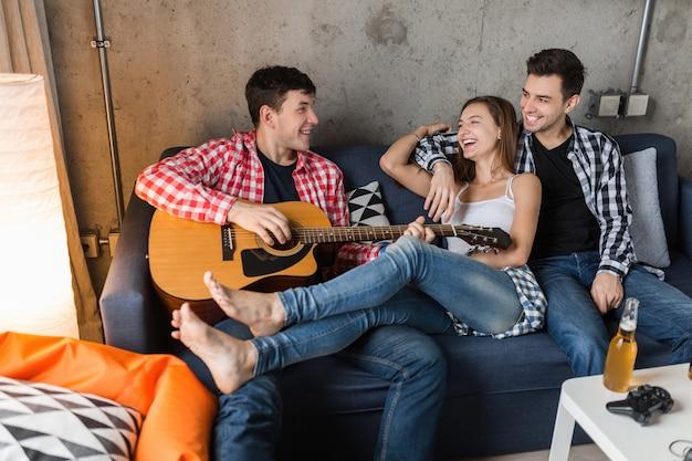 Gelukkige jonge mensen die lol hebben, vrienden feesten thuis, hipster gezelschap samen, twee mannen een vrouw, gitaar spelen, glimlachen, positief, ontspannen, bier drinken, jeans, shirts, casual stijl