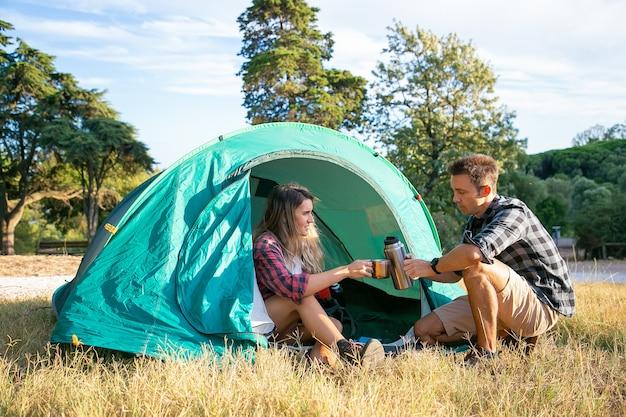 Gelukkige jonge mensen die op gazon kamperen en in tent zitten. twee reizigers en vrienden die thee drinken uit een thermoskan. vrouw met paal. backpacken toerisme, avontuur en zomervakantie concept