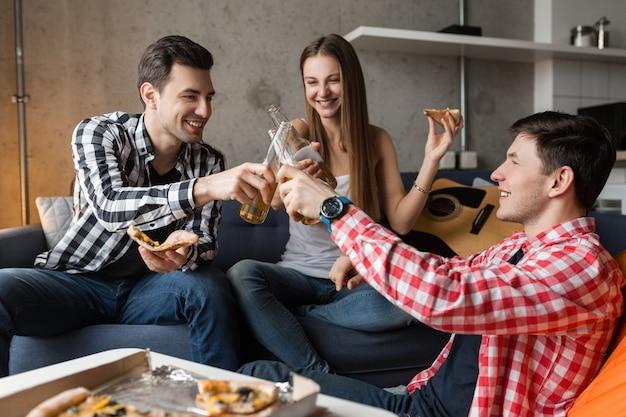 Gelukkige jonge mensen die pizza eten, bier drinken, plezier maken, vriendenfeestje thuis, hipster gezelschap samen, twee mannen één vrouw, glimlachen, positief, ontspannen, rondhangen, lachen,