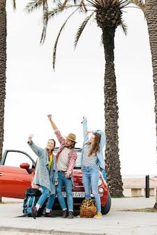 Gelukkige jonge mensen die selfie dichtbij rode auto in straat nemen
