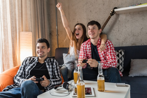 Gelukkige jonge mensen die videogames spelen, plezier hebben, vriendenfeestje thuis, hipster gezelschap samen, twee mannen één vrouw, glimlachen, positief, ontspannen, emotioneel, lachen, competitie