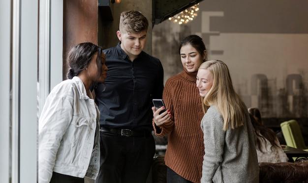 Gelukkige jonge mensen kijken naar een video op een mobiele telefoon