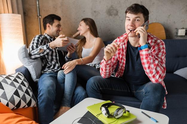 Gelukkige jonge mensen met behulp van tablet, studenten leren, plezier hebben, vriendenfeestje thuis, hipster bedrijf samen, twee mannen een vrouw, glimlachen, positief, online onderwijs, man praten over de telefoon